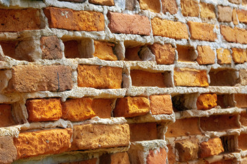 Old front wall with weather-beaten bricks