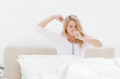 Woman sitting upright in bed, stretching her arms as she wakes u