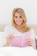 Close up shot, Woman sitting in bed, book in hand as she looks f