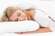 Woman lying in bed with her head resting on the pillow and her h