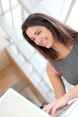 Portrait of smiling student girl working on laptop