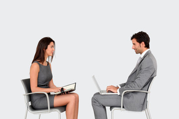 Business people sitting face to face on grey background