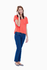 Teenager standing against a white background while giving a call