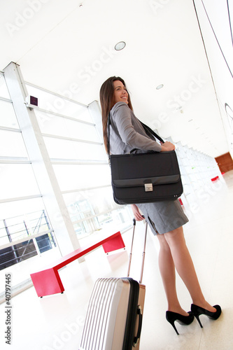 Smiling businesswoman pulling cabin suitcase in hallway