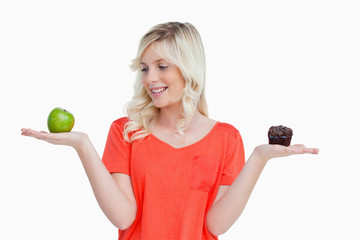 Young woman holding an apple and a muffin while looking at the a