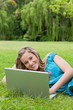 Young smiling girl using her laptop while lying on the grass