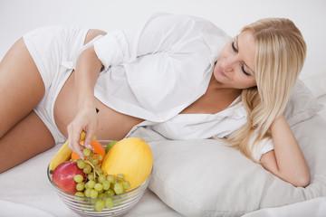 schwangere frau liegt bequem und nascht am obstkorb