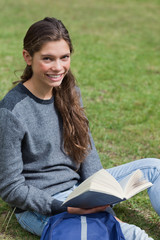 Smiling young adult holding an open book while sitting on the gr