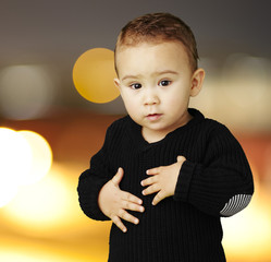 portrait of adorable kid touching his stomach at city by night