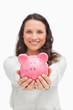 Brunette showing a piggy bank