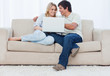 A young couple sitting on a couch with a laptop