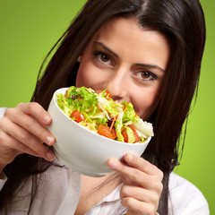 portrait of young woman holding a fresh salad over green