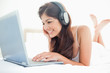 Woman watching her laptop screen and listening to her headphones