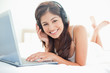 Woman looking ahead smiling, while using a laptop and headphones