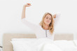 Woman upright in bed stretching with arm raised and eyes closed