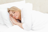 Woman sleeping in bed with hands placed beside her head on the p