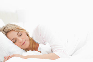 Woman sleeping in bed, with her arm resting slightly in front of