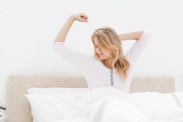 Woman in bed stretching as she wakes up from sleeping