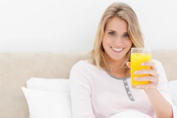 Woman holding a glass of orange juice while smiling and looking