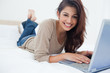 Woman smiling as she lies on the bed with her laptop in front of