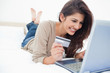 Woman on her laptop with credit card in hand and smiling