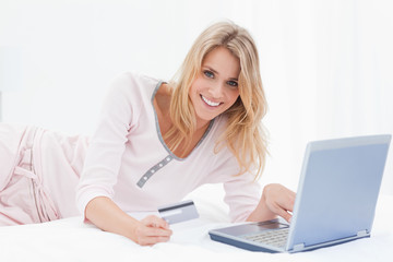 Woman lying on the bed with her laptop and credit card and smili