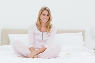 Woman sitting with her legs folded on the bed while smiling