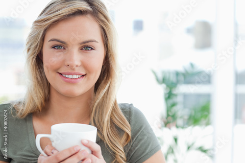 Woman holding a mug in her hands and smiling, while looking forw
