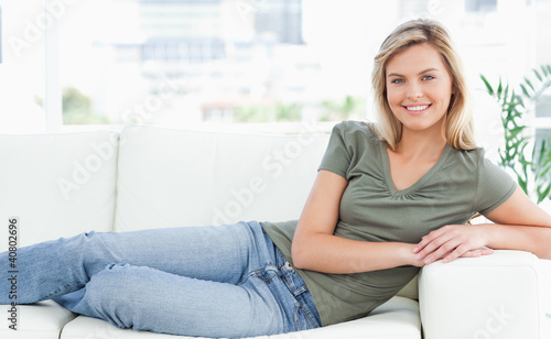 Woman lying across the couch, looking forward, smiling with arms