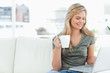 Woman smiling as she holds her cup and uses her laptop