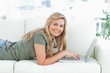 Woman smiling as she lies on the couch while using her laptop