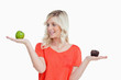 Woman imitating the food-balance to choose between an apple and