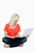 Young blonde woman sitting cross-legged with her laptop on her l