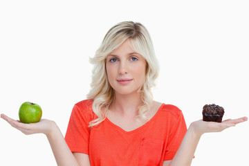 Young woman looking at the camera while holding a muffin and a g