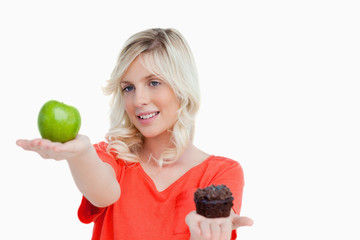 Woman looking at her favorite food between apple and muffin