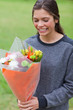 Smiling teenage receiving a bunch of flowers