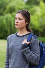 Thoughtful young girl standing in the countryside while carrying