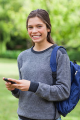 Smiling teenage girl standing upright while sending a text