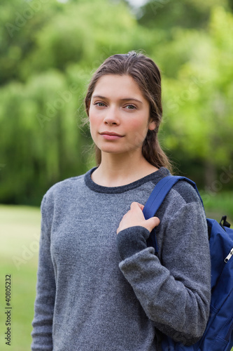 Young relaxed girl looking straight at the camera while standing