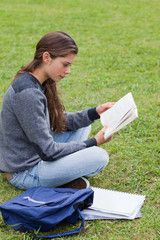 Young serious girl reading a book while sitting cross-legged