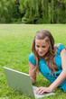 Smiling teenager lying in a park while typing on her laptop