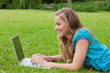 Young smiling girl looking at her laptop while lying down