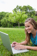 Young smiling girl using her laptop in a park while lying on the