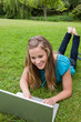 Smiling student working on her laptop in a park while lying with