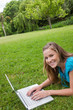 Smiling girl lying in a public garden while working on her lapto