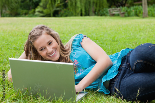 Young smiling girl lying on the side in a park while typing on h