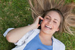 Young laughing girl lying on her back while talking on the phone