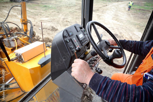 Driver in grader at construction site