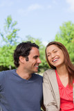 Man looking his friend as she is laughing joyfully while sitting