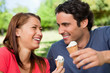 Two friends laughing while holding ice cream